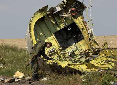 FILE - In this July 22, 2014 file photo, a pro-Russian rebel touches the MH17 wreckage at the crash site of Malaysia Airlines…