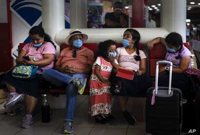 Tourists from Mexico wearing masks as a precaution against the spread of the new coronavirus, wait for their flight home, at…