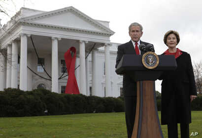 President George W. Bush makes a statement with first lady Laura Bush, right, on World AIDS Day, at the White House in…