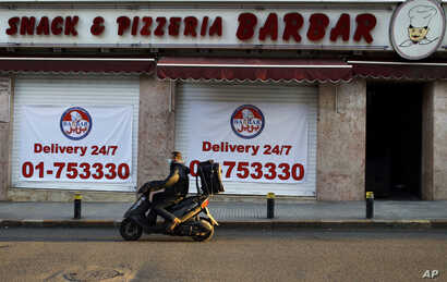 In this Saturday, March 21, 2020 photo, a food delivery scooter passes Barbar Restaurant that now offers food for delivery only…