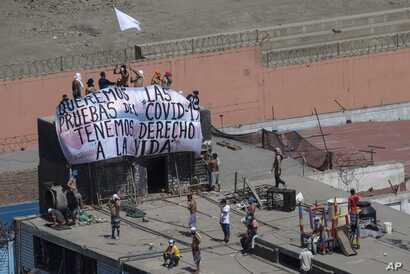 """Inmates hold a sign that reads in Spanish """"We want COVID-19 tests, we have the right to live"""","""" as they gather ona roof during…"""