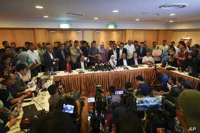 In this Feb. 22, 2020, photo, Malaysian Prime Minister Mahathir Mohamad, center right, speaks during a press conference in…