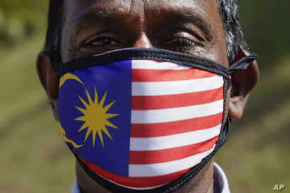 A supporter of People's Justice Party wearing a national flag face mask as he gathers with others outside the National Palace…