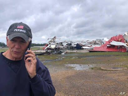 In this photo provided by Rep. Ralph Abraham, R-La., he is seen talking on his phone in front of a destroyed hangar and damaged…