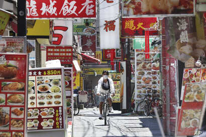 A man wearing a face mask to protect against the spread of the new coronavirus cycles through China Town in Yokohama, near…
