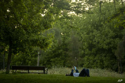 A man holds a face mask as he rests in a public park in Madrid, Spain, Wednesday, May 6, 2020. Spain has this week started to…