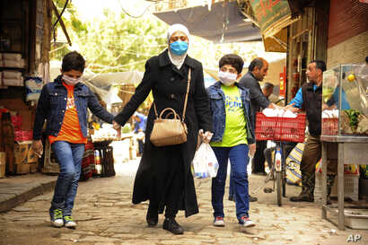 In this photo released on Saturday April 18, 2020, by the Syrian official news agency SANA, shows a Syrian woman with her sons…