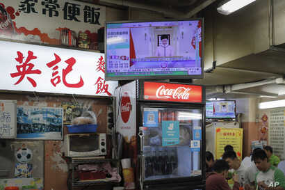People eat lunch near a television broadcasting Hong Kong Chief Executive Carrie Lam's speech live at a restaurant in Hong Kong…