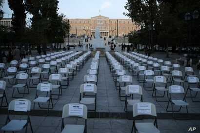 Empty chairs with various slogans from the union of bars and restaurants owners are placed at Athens' main Syntagma square…