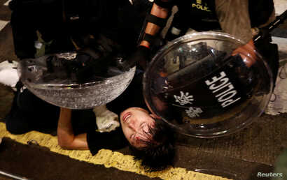 A demonstrator is detained by police officers during a protest in Hong Kong, Aug. 31, 2019.
