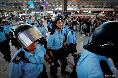 Riot police walk inside the airport as anti-extradition bill protesters gather outside, in Hong Kong, China September 1, 2019. REUTERS/Tyrone Siu
