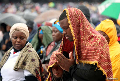 The faithful pray in the rain as Pope Francis holds Holy Mass at Zimpeto stadium in Maputo, Mozambique, September 6, 2019. REUTERS/Mike Hutchings