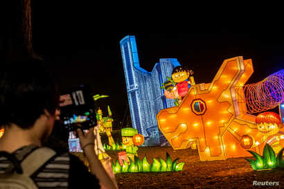 A woman uses her smartphone to take pictures of a lantern display depicting Singapore's iconic architecture and multiracial society during Mid-Autumn Festival celebrations at Jurong Lake Gardens in western Singapore, September 9, 2019. Picture taken September 9, 2019. REUTERS/Loriene Perera