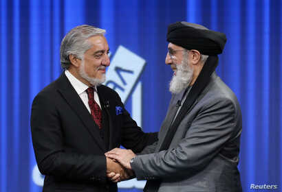 Afghan presidential candidates Abdullah Abdullah and former Afghan warlord Gulbuddin Hekmatyar shake hands before the presidential election debate at TOLO TV studio in Kabul, Afghanistan September 25, 2019. REUTERS/Omar Sobhani