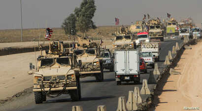 A convoy of U.S. vehicles is seen after withdrawing from northern Syria