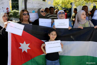 A girl holds placard in front of a Jordanian national flag as public schools' teachers take part in a protest in Amman, Jordan…