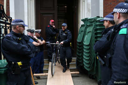 A police officer removes a bicycle outside Lambeth County Court, during a raid on an Extinction Rebellion storage facility, in…