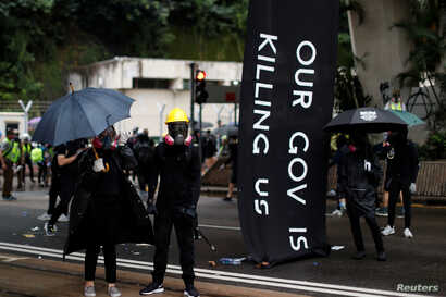 Masked protesters hold umbrellas during an anti-government rally in central Hong Kong, China October 6, 2019. REUTERS/Jorge…