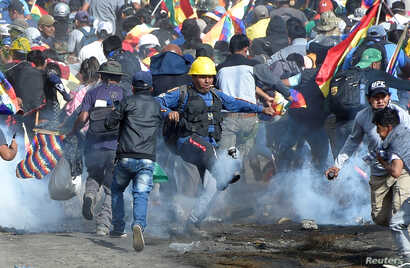 Coca growers, supporters of former President Evo Morales, run away from tear gas as one of them kicks a tears gas canister…