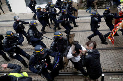 Protesters clash with French riot police during a demonstration to mark the first anniversary of the