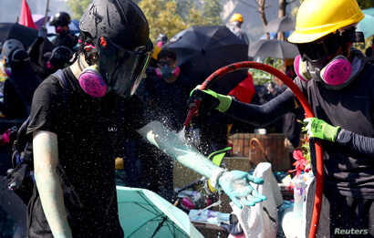 Anti-government protesters clean off blue liquid from the police's water cannon outside Hong Kong Polytechnic University (PolyU…