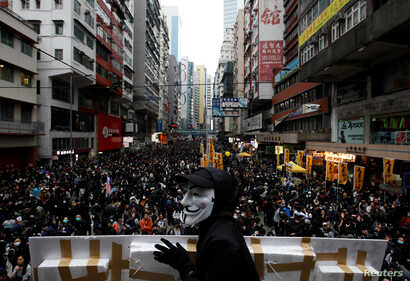 An anti-government protester wears a Guy Fawkes mask during a demonstration on New Year's Day to call for better governance and…