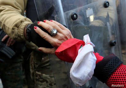 A protestor holds the hand of a Lebanese army soldier during a protest against the political elite in Beirut, Lebanon January…