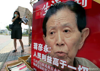 A Chinese woman adjusts her face mask at a newspaper stall featuring a photo of Dr. Jiang Yanyong in Beijing June 5, 2003. At a…