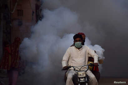 Health workers on motor-bike fumigate, as a preventive measure against coronavirus, along a street in Hyderabad, Pakistan March…