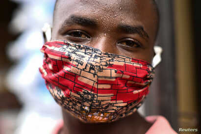 "Pierre Mahiraguha, a vendor at the Kimironko market wears a handmade ""kitenge"" cloth mask as he attempts to protect against the…"