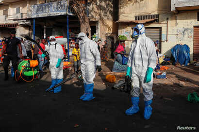 Members of local hygiene services wear protective suits and face masks as they prepare to disinfect the street and market to…