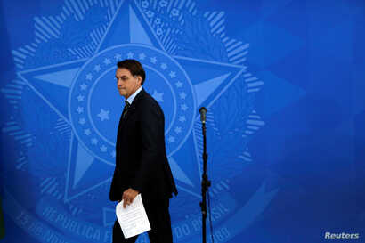 Brazil's President Jair Bolsonaro walks after a meeting with the governors to define strategies to combat to COVID-19 during…
