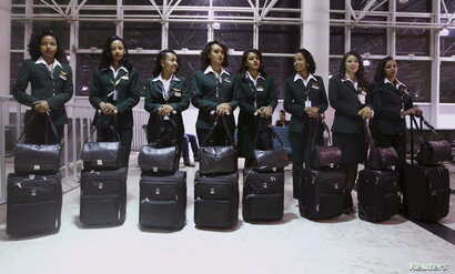 Ethiopian Airlines cabin crew members wait to get onboard the plane before takeoff at Bole international airport in the capital…
