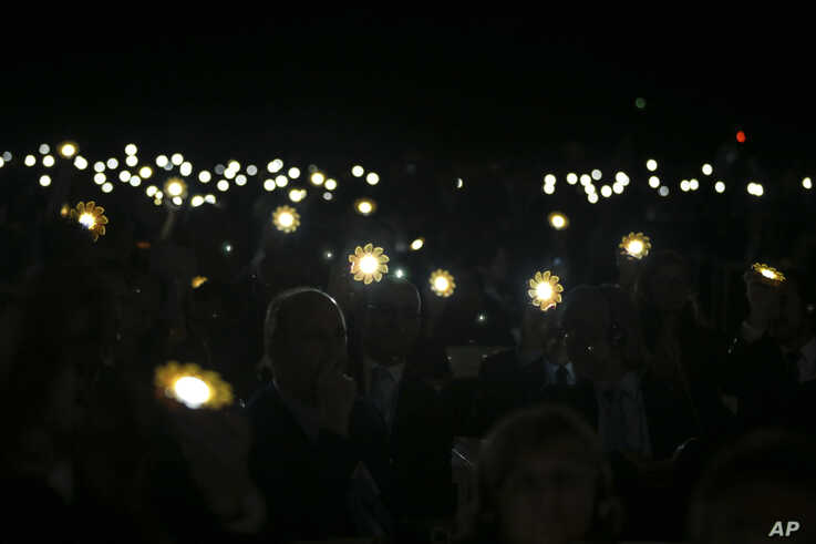 Participants and delegate members hold up solar lanterns in honor to the Paris Agreement, during the opening session of the Climate Conference in Marrakech, Morocco, Nov. 7, 2016.