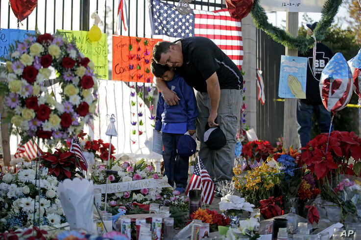 Gary  Mendoza, and his son Michael pay their respects at a makeshift memorial site honoring Wednesday's shooting victims Monday, Dec. 7, 2015, in San Bernardino, California.