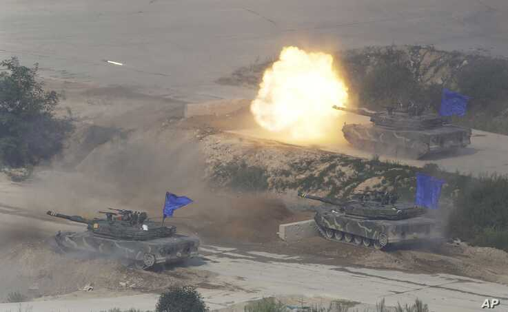 South Korean K1A1 battle tanks fire during the South Korea-U.S. joint military drills at Seungjin Fire Training Field in Pocheon, South Korea, near the border with North Korea, Friday, Aug. 28, 2015.