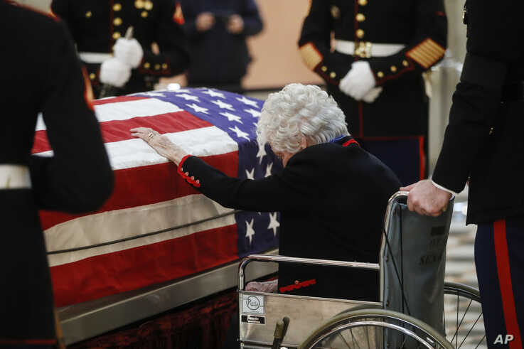 Annie Glenn touches the casket of her husband, John Glenn, as he lies in repose at the Ohio Statehouse in Columbus, Dec. 16, 2016. Glenn's home state and the nation began saying goodbye to the famed astronaut, who died last week at age 95.