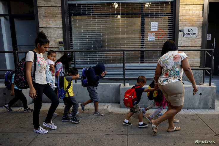 Children cover their faces as they are escorted to the Cayuga Center, which provides foster care and other services to immigrant children separated from their families, in New York City, July 10, 2018.