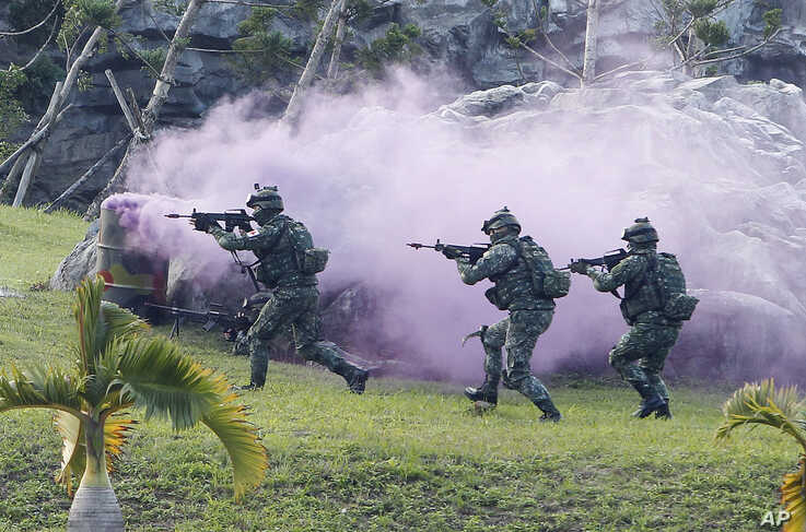 Soldiers from Taiwan's special forces move past colored smoke during a helicopter landing training and all-out defense demonstration in Taipei, Taiwan, Dec. 14, 2017.