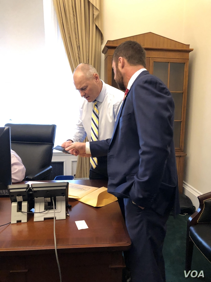 Rep. Pete Stauber (R - Minn) is coached by veteran congressman on usefulness of Capitol ID badges, car license plates. (Photo: Carolyn Presutti / VOA)