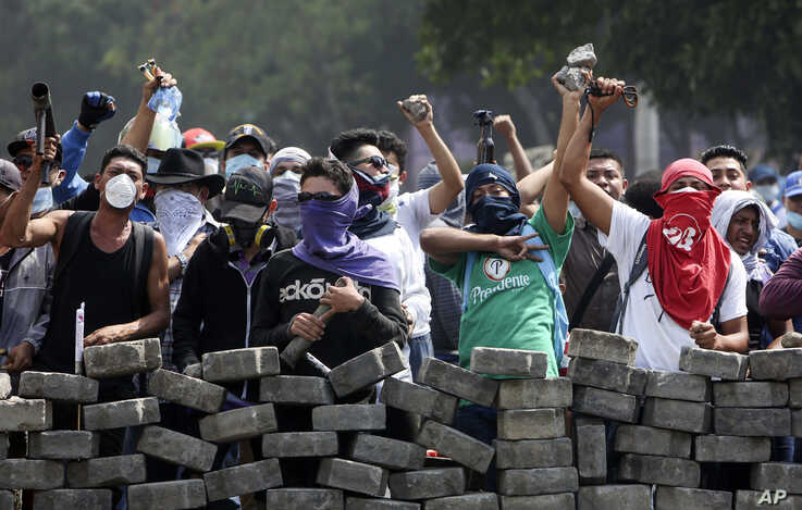 Protesters yell from behind the roadblock they erected as they face off with security forces near the University Politecnica de Nicaragua in Managua, Nicaragua, April 21, 2018. Nicaragua's government said it is willing to negotiate over controversial...