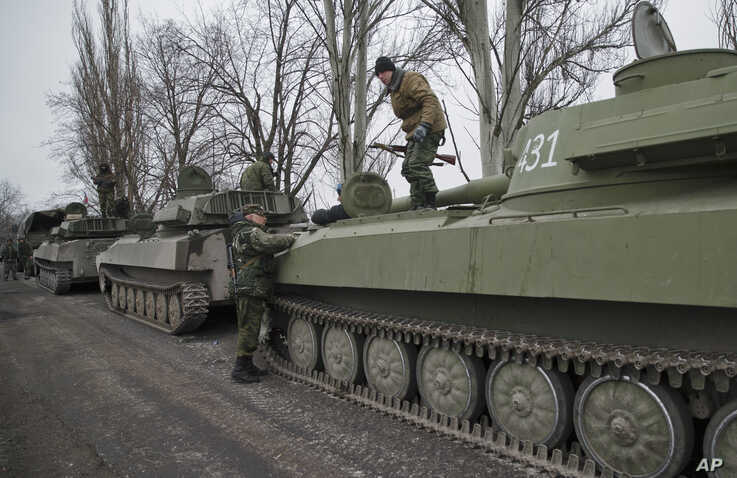 Russia-backed separatist fighters stand on self propelled 152 mm artillery pieces, part of a unit moved away from the front lines, in Yelenovka, near Donetsk, Ukraine,Thursday, Feb. 26, 2015. Russia's foreign minister is sharply criticizing Ukraine's