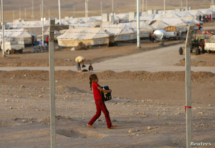 A displaced child from the minority Yazidi sect, who fled violence in the Iraqi town of Sinjar, carries a jerry can filled with water at Bajed Kadal refugee camp southwest of Dohuk September 15, 2014.   REUTERS/Ahmed Jadallah (IRAQ - Tags: CIVIL UNRE