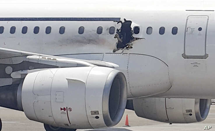 A gaping hole is visible in the side of a plane operated by Daallo Airlines as it sits on the runway of the airport in Mogadishu, Somalia, Feb. 2, 2016.