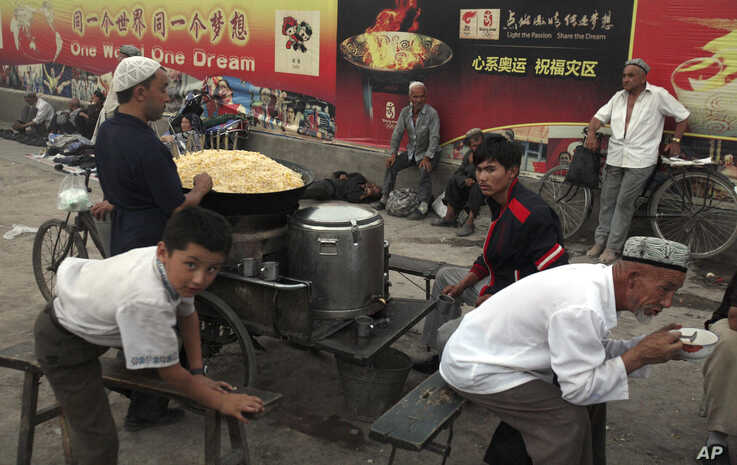 FILE - Uighurs rest near a food stall and Beijing Olympic Games billboards in Kashgar in China's western Xinjiang province, Aug. 6, 2008. Human Rights Watch said Tuesday, May 16, 2017, that China appears to be laying the groundwork for the mass colle