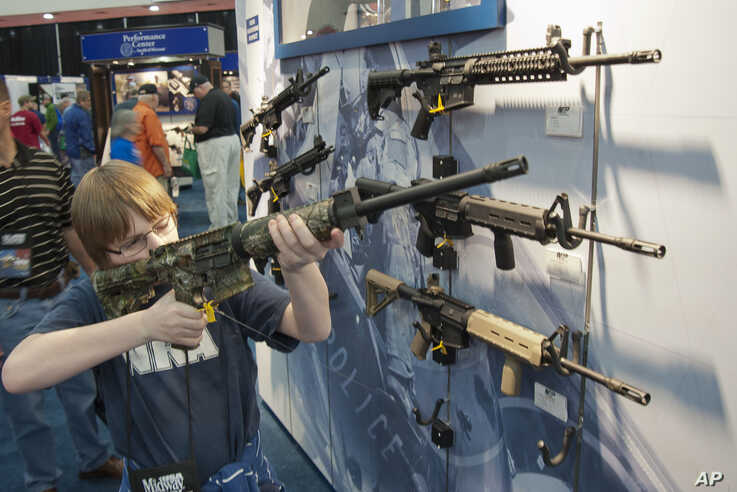 A young man, who chose not to give his name, sizes-up an assault style rifle during the National Rifle Association's annual convention in Houston, Texas, May 3, 2013.