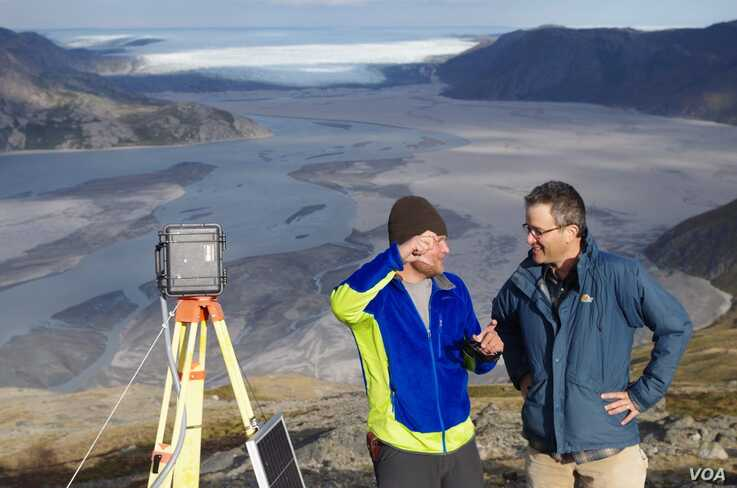 UCLA geography graduate student Lincoln Pitcher (left) and UCLA geography professor Laurence C. Smith overlook the mighty Isortoq River, where meltwater leaves the Greenland ice sheet to flow to the ocean seen in the distance. (UCLA/Lawrence C. Smith