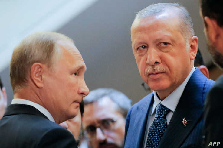 Russian President Vladimir Putin, left, and Turkish President Recep Tayyip Erdogan wait to enter a hall during their meeting at the Bocharov Ruchei residence in the Black Sea resort of Sochi, in Sochi, on Sept. 17, 2018.