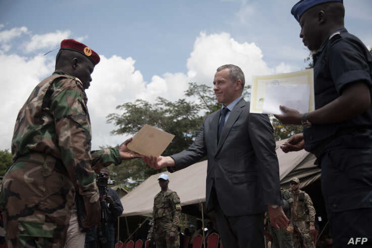 FILE - Victor Tokmakov, First Secretary of the Russian Embassy, presents graduation diplomas to graduating recruits in Berengo, Central African Republic, Aug. 4, 2018. Russian military consultants set up training for the Central African Armed Forces