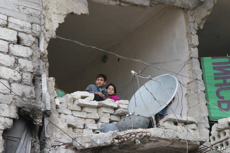 FILE - Children peer from a partially destroyed home in Aleppo, Syria, Feb. 11, 2016. More than 100 children have been reported killed in the last couple of weeks as Syrian and Russian warplanes sought to bombard into submission the rebel eastern dis...